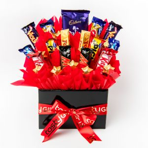 A variety of chocolate bars accompanied by 13 gold foil wrapped milk chocolate hearts, surrounded by red cello in a large black box.