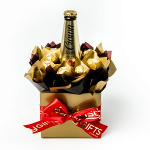 "8 Ferrero Rocher chocolates wrapped in clear and ""leafed"" in gold cello, all neatly tucked around a bottle of Crown Lager, surrounded by gold and brown cello in a small gold box."