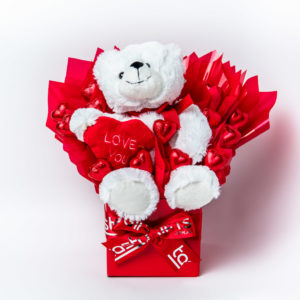 A Cuddles Bear soft toy and 13 red foil wrapped milk chocolate hearts surrounded by red cello in a small red box.