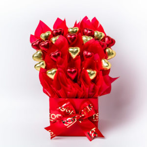 22 red and gold foil wrapped dark chocolate hearts surrounded by red cello in a small red box.