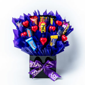 10 Favourites chocolates and 7 red foil wrapped milk chocolate hearts surrounded by purple cello in a small black box.