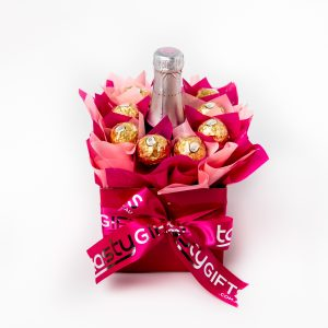 "A Yellowglen pink piccolo surrounded by 10 Ferrero Rocher chocolates ""leafed"" in pink and baby pink cello in a small pink box. Finished with a pink ribbon with gold print."