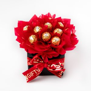 "13 Ferrero Rocher chocolates wrapped in clear and ""leafed"" in red cello, surrounded by red cello in a small black box."