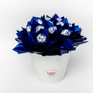 "13 Baci chocolates wrapped in clear cello and ""leafed"" in royal blue cello surrounded by royal blue cello in a small white keepsake metal bucket."