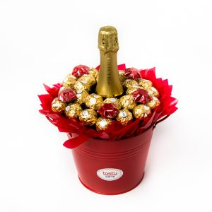 26 Ferrero Rocher chocolates and 5 red foil wrapped milk chocolate stars around a 750ml bottle of Wolf Blass Bilyara sparkling brut surrounded by red cello in a large red keepsake metal bucket.