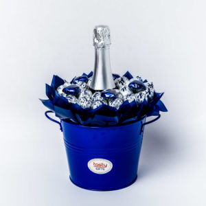 26 Baci chocolates and 5 blue foil wrapped milk chocolate hearts around a 750ml bottle of Stony Peak sparkling brut surrounded by blue cello in a large blue keepsake metal bucket.