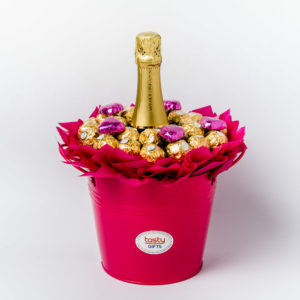 26 Ferrero Rocher chocolates and 5 pink foil wrapped milk chocolate hearts around a 750ml bottle of Wolf Blass Bilyara sparkling brut surrounded by pink cello in a large pink keepsake metal bucket.