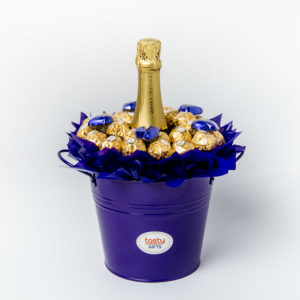 26 Ferrero Rocher chocolates and 5 purple foil wrapped milk chocolate hearts around a 750ml bottle of Wolf Blass Bilyara sparkling brut surrounded by purple cello in a large purple keepsake metal bucket.