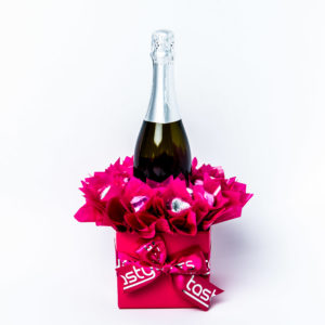 A 750ml bottle of Stony Peak sparkling brut NV with 20 pink and silver foil wrapped milk chocolate hearts, surrounded by pink cello in a small pink box.