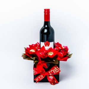 A 750ml bottle of Jarvis Estate red wine with 20 red and gold foil wrapped milk chocolate stars, surrounded by red and gold cello in a small black box. Finished with a red ribbon with gold print.