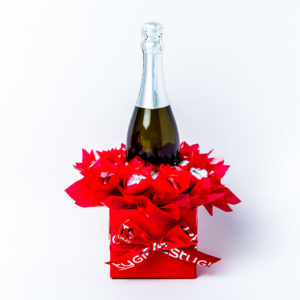 A 750ml bottle of Stony Peak sparkling brut NV with 20 red and silver foil wrapped milk chocolate hearts, surrounded by red cello in a small red box.