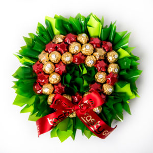 18 Ferrero Rocher chocolates and 21 red and gold foil wrapped milk chocolate stars surrounded by green cello in a wreath shape.