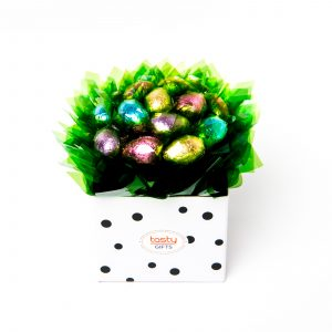 "15 Milk chocolate half eggs wrapped in clear and ""leafed"" in green, surrounded by green cello in a small white polka dot box."